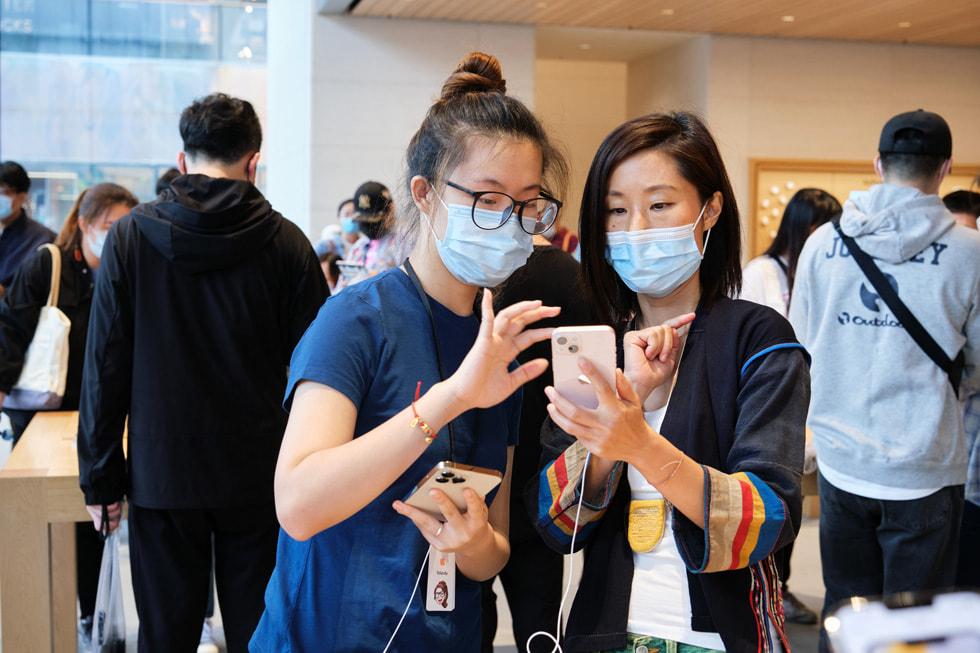 Apple 三里屯零售店团队成员帮助顾客选购 iPhone 13。