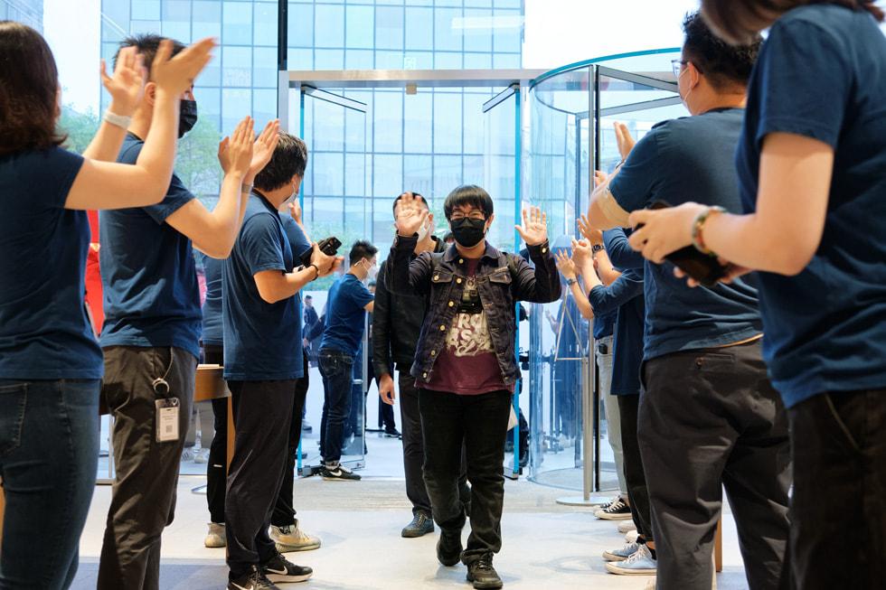 Apple 三里屯零售店团队成员热烈欢迎顾客前来体验 iPhone 13 系列机型。
