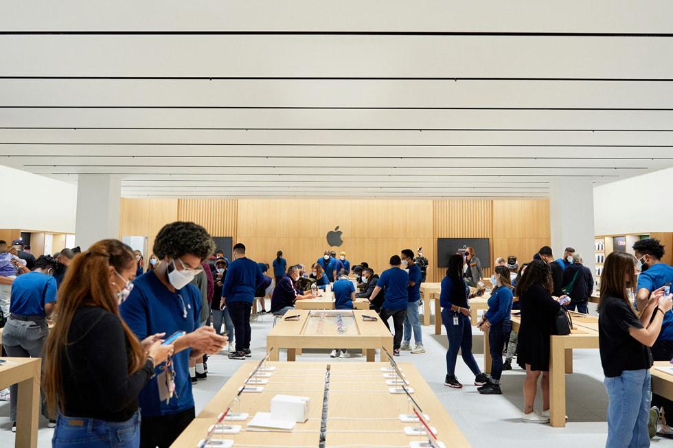 Apple Bay Plaza 零售店内,顾客与 Apple 团队成员围绕在展示台旁。