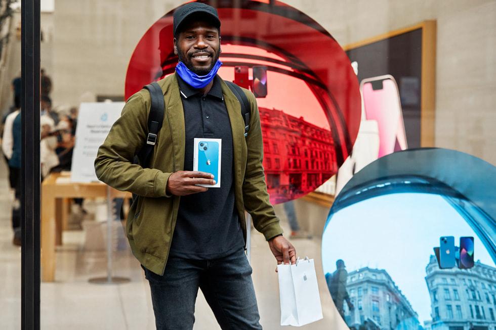 Apple Regent Street 零售店内,一名顾客正在展示自己新购入的 iPhone 13。