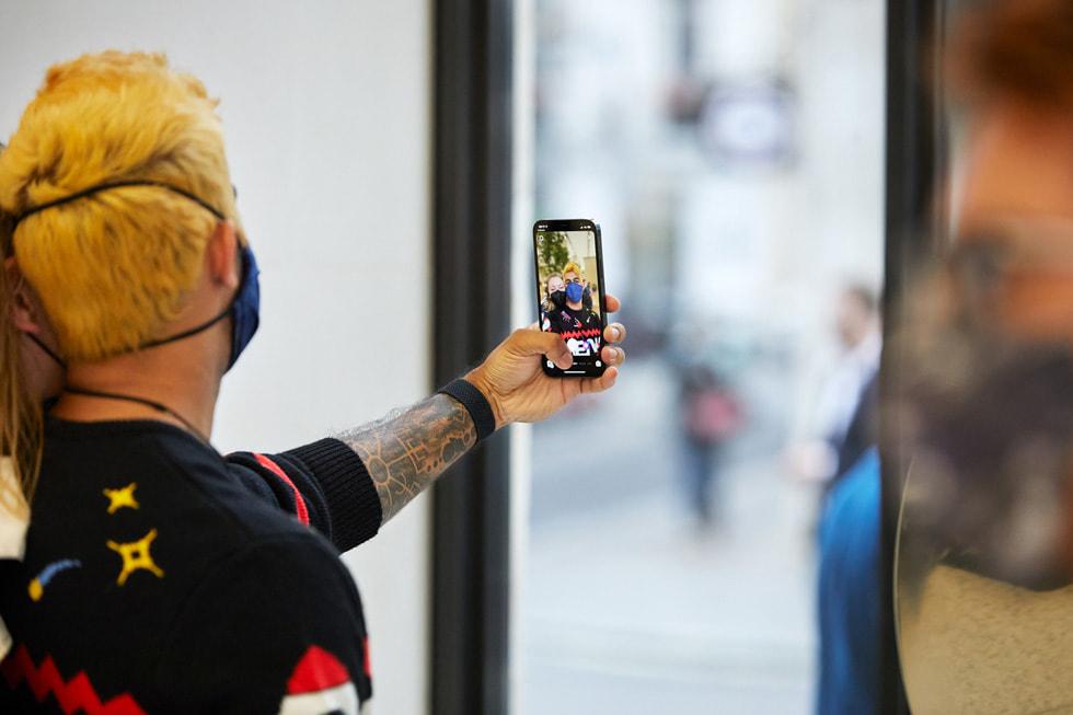 Apple Regent Street 零售店内,顾客正在使用新款 iPhone 13 Pro 自拍。