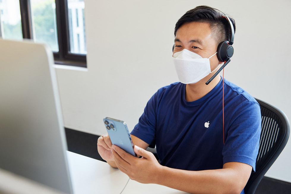 在 Apple 位于上海的呼叫中心,一位 Apple 在线团队成员正在为顾客介绍新款 iPhone 13 Pro Max。