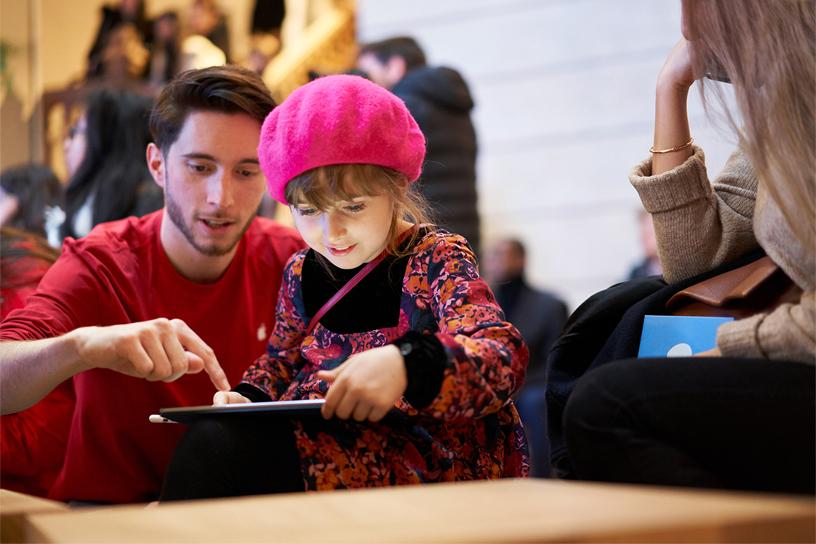 Apple 员工向小女孩展示如何使用 iPad。