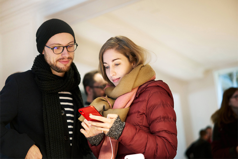 两名顾客正在使用红色版 iPhone XR。
