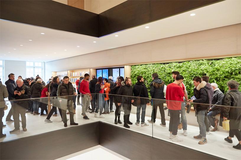 Apple Champs-Élysées 的员工和顾客站在绿植墙前面。