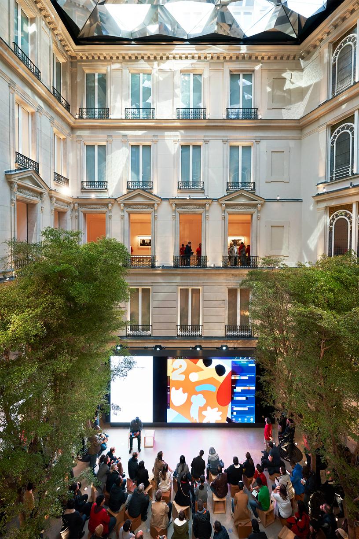 一群顾客坐在 Apple Champs-Élysées 的 Forum 互动坊中。