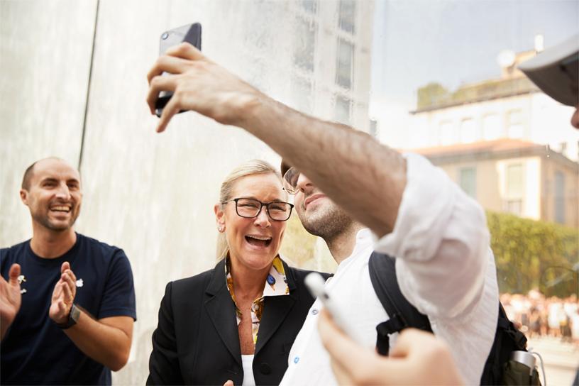 Apple 零售业务高级副总裁 Angela Ahrendts 向玻璃喷泉入口内的顾客表示欢迎。