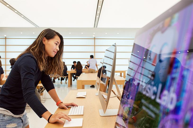 一位女士在 Apple Kyoto 使用 iMac 和妙控板。