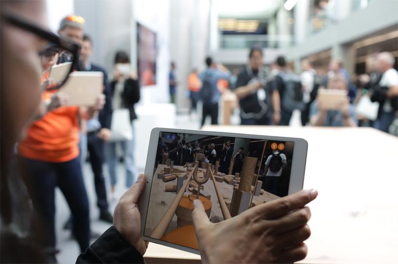 一位 iPad 用户正在玩 SwiftShot,体验屏幕上的增强现实画面。