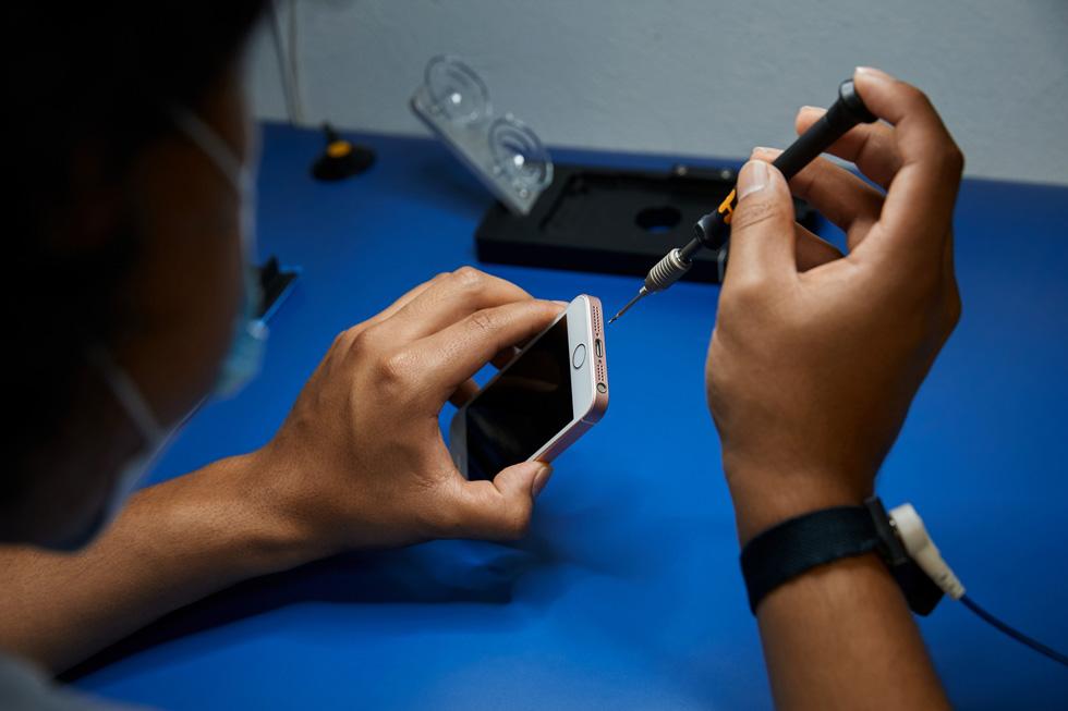 一名技术人员正在维修一部 iPhone。