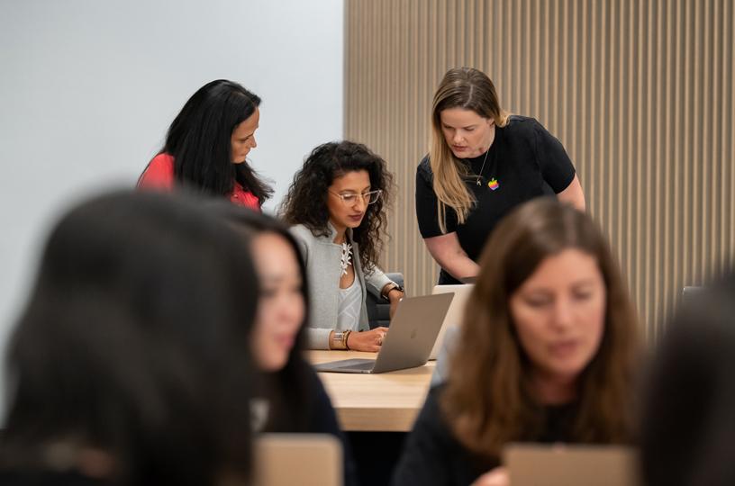 一名女性在两位讲师的指导下使用 MacBook