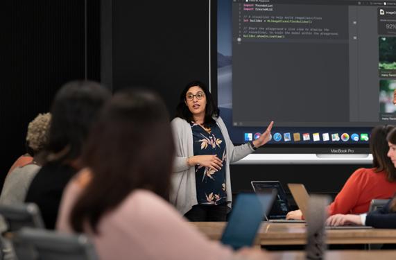 一名讲师在学员前通过 MacBook Pro 展示编程。