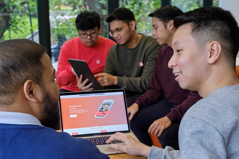 学生正在使用 MacBook Pro 和 iPad。