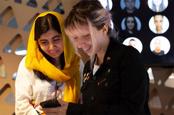Malala Yousafzai 在里约 Apple 开发者学院与一名女士一同看着一部 iPhone。