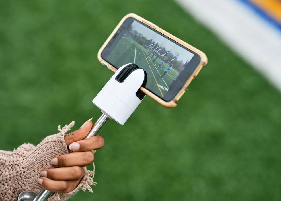 一名新罗谢尔高中学生使用 iPad 录制运动场上旗手的视频。