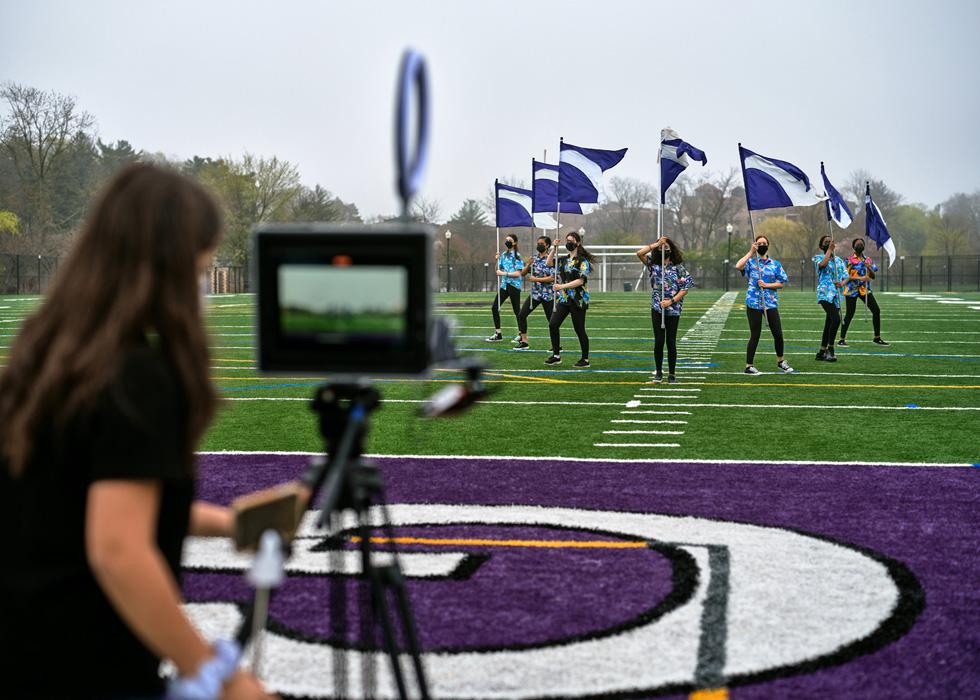 一名新罗谢尔高中学生使用 iPad 拍摄运动场上举着旗帜的学生们。