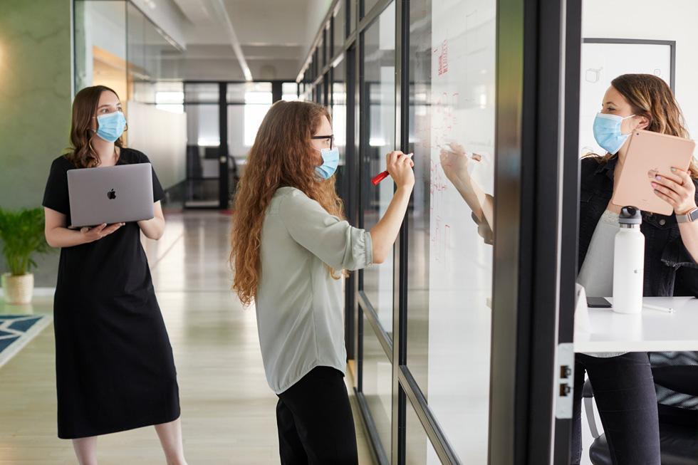ImagiLabs 创始人 Paula Dozsa、Beatrice Ionascu 和 Dora Palfi 正在使用 Mac、iPad 和白板协同工作。