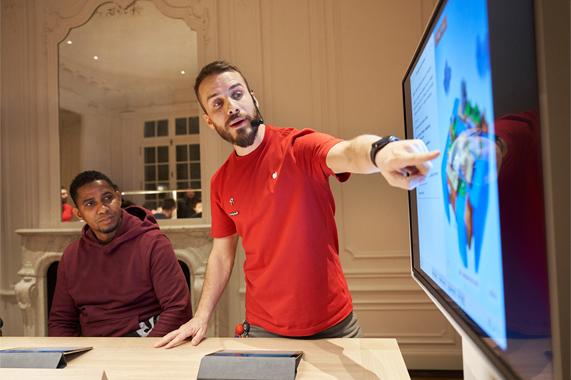 一名 Apple 员工正在为顾客进行演示。