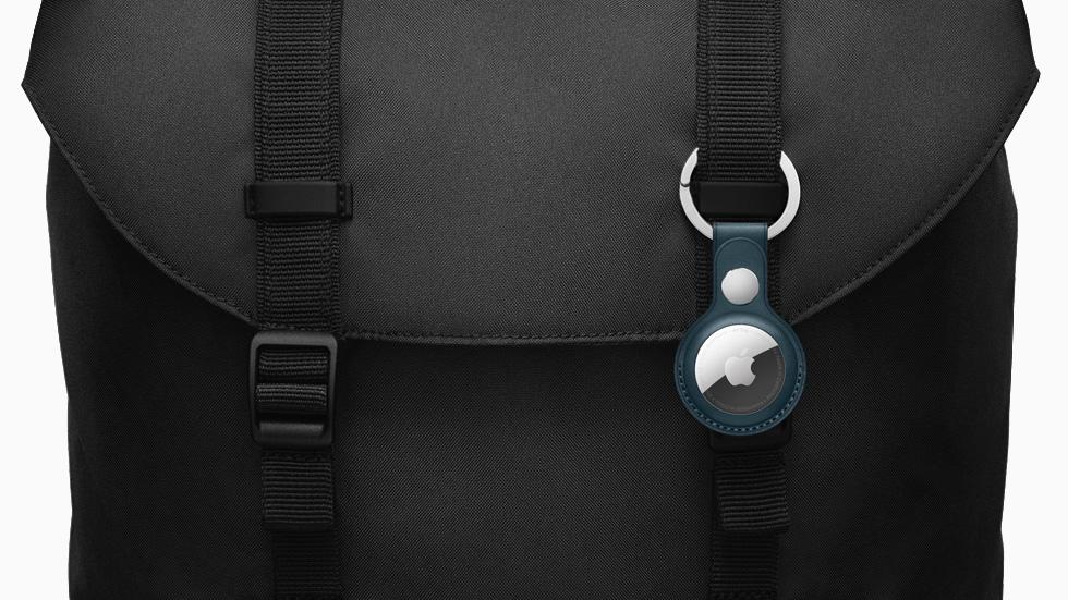 配有皮革钥匙扣的 AirTag 挂在斜跨包上。
