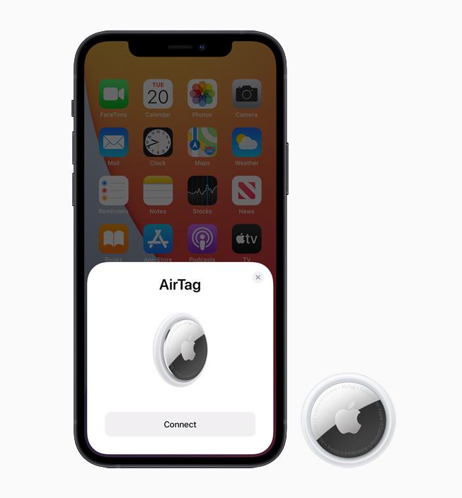 一部显示 AirTag 设置页面的 iPhone 12 与一枚 AirTag 设备。