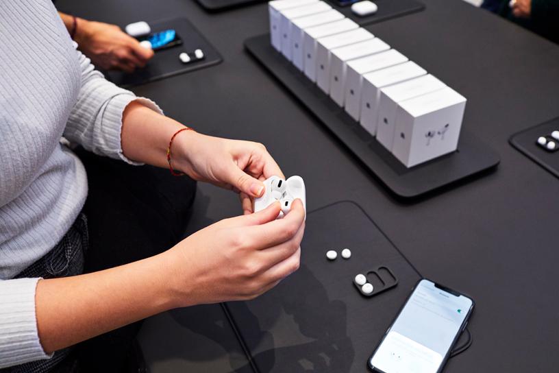 米兰 Apple Piazza Liberty 店内,一位顾客打开展示桌上的 AirPods Pro。
