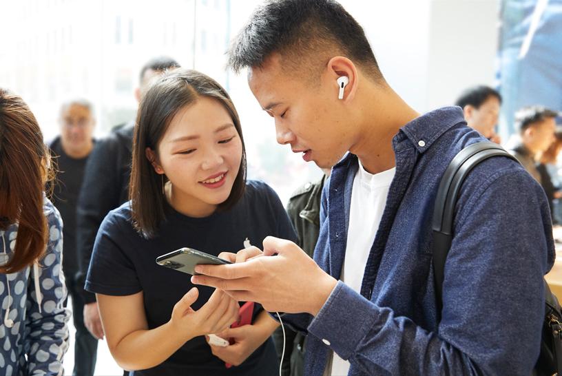 上海 Apple 南京东路店内,一位顾客在与 Apple 工作人员交谈。