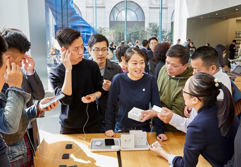 上海 Apple 南京东路店内,多位顾客围聚在桌前。