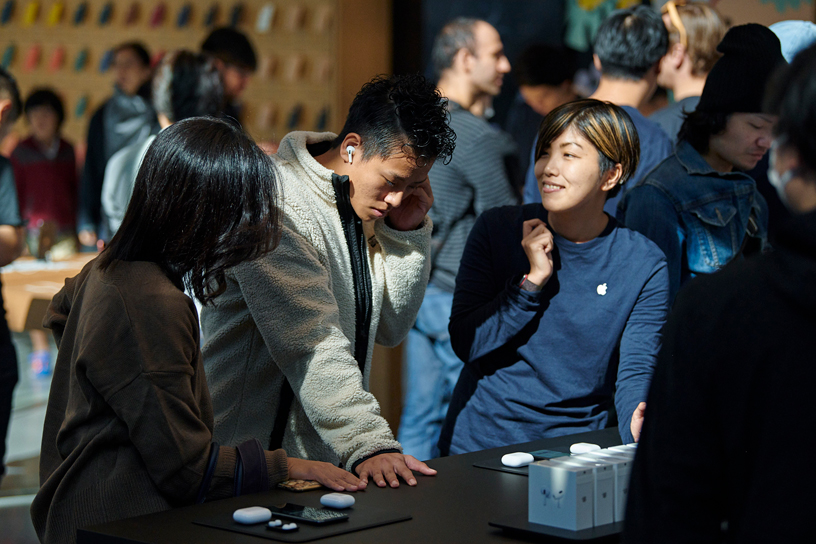 东京 Apple 表参道店内,顾客在 Apple 团队的帮助下试戴 AirPods Pro。