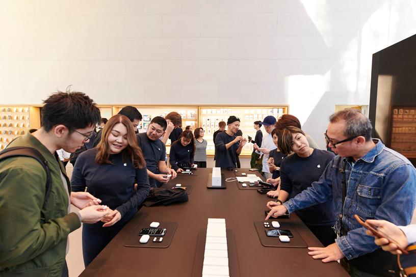 东京 Apple 表参道店内,Apple 工作人员在桌前为顾客提供帮助。