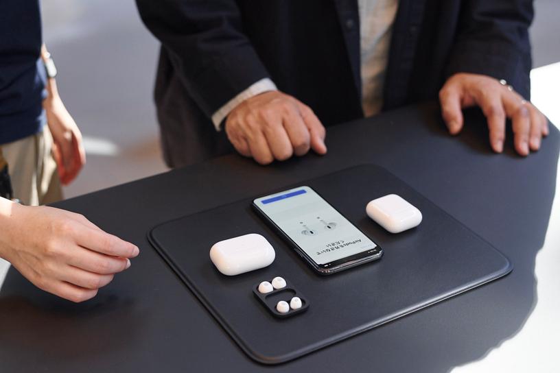 东京 Apple 表参道店内的一张桌子上,摆放着多个 AirPods Pro 充电盒和一台 iPhone。