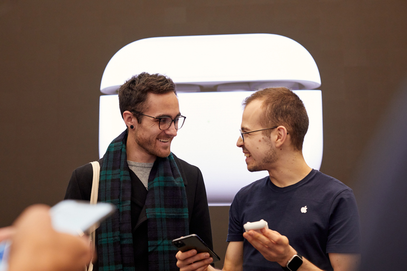 伦敦 Apple Regent Street 店内,一位工作人员协助顾客设置 AirPods Pro。