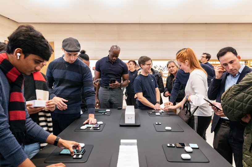 纽约 Apple Fifth Avenue 店内,顾客聚集在 AirPods Pro 展示桌周围。