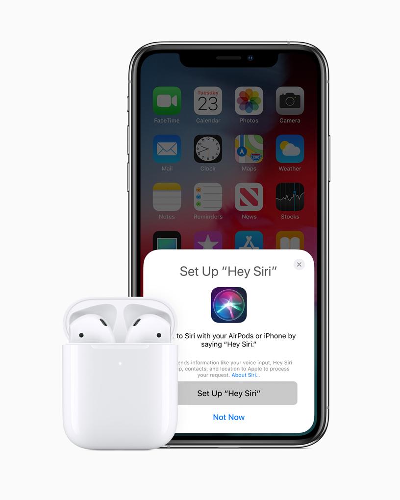 AirPods 置于充电盒内,放在 iPhone 旁。