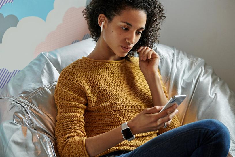 一名女性在沙发上手拿 iPhone 聆听 AirPods。