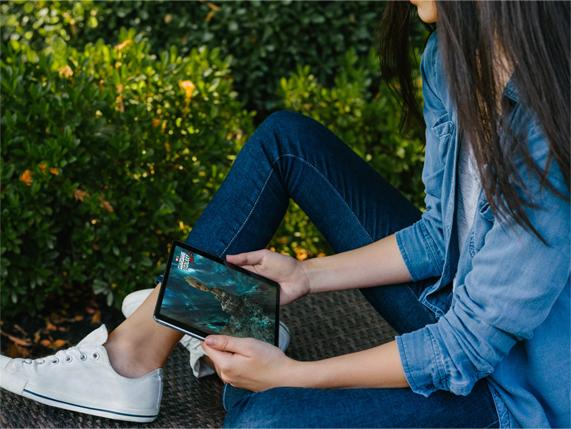 一位女士在室外使用 iPad 看电影。
