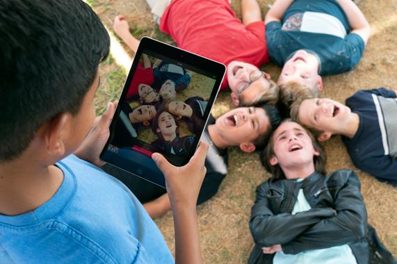学生用 iPad 给同学拍照。