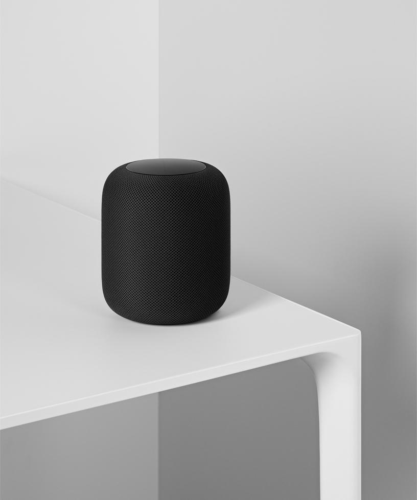 图片显示黑色的 HomePod 放在白色桌面上。