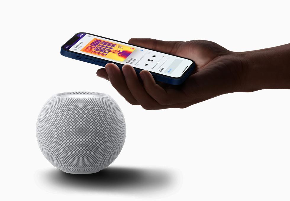 一位用户手握 iPhone 12 靠近 HomePod mini。