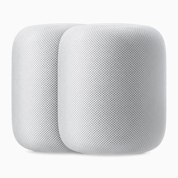 两只白色 HomePod 扬声器。