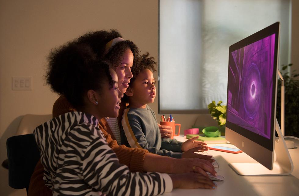 一位女性在使用鼠标操作 27 英寸 iMac,两个孩子在旁边看着屏幕。