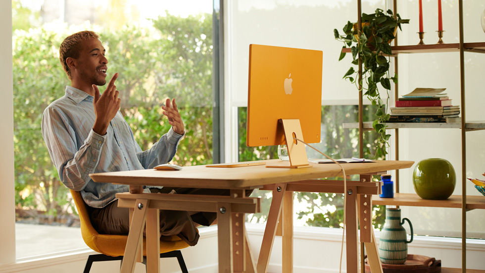 一名男性在家庭办公室里使用橙色的新款 iMac。