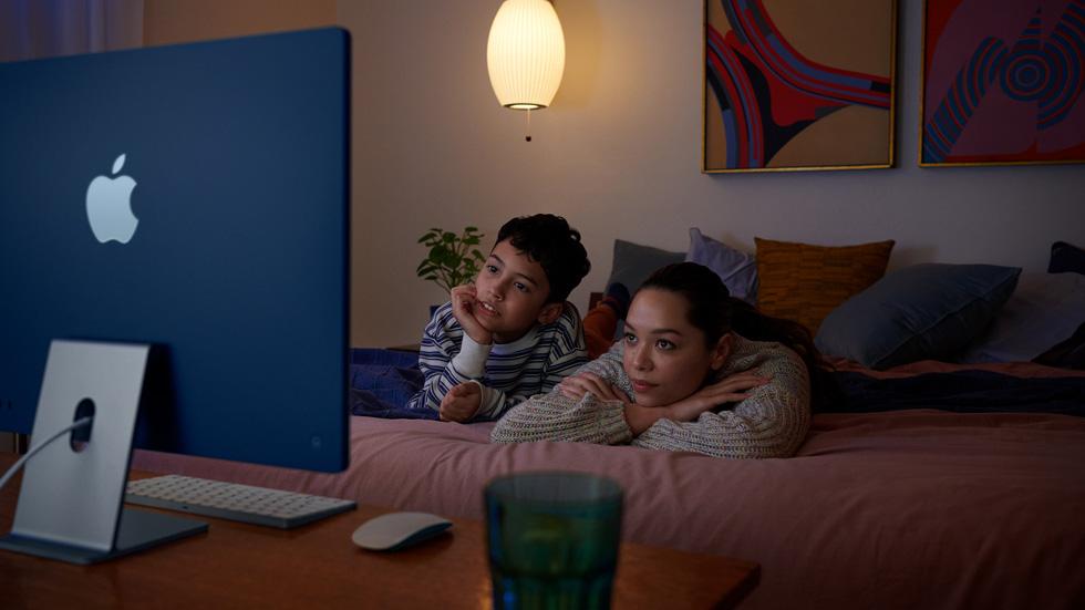 一名女性和一个孩子躺在床上,用新款 iMac 观看节目。