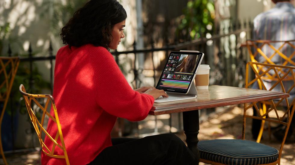 一位女性正在使用搭配白色妙控键盘的 iPad Pro。
