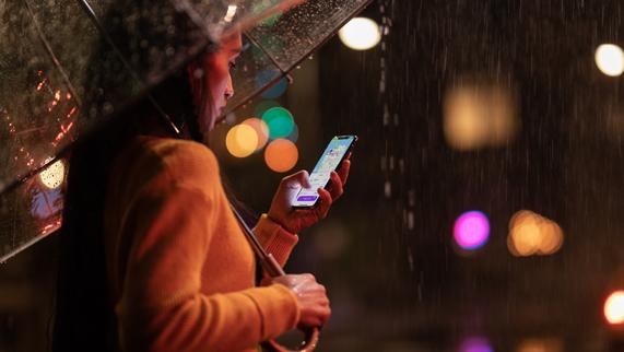 雨中的女子手拿一把雨伞和一部 iPhone Xs。