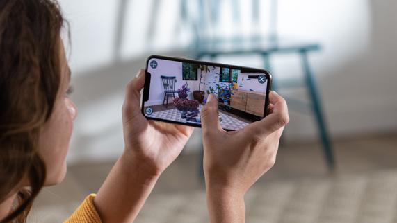 女子手握显示增强现实画面的 iPhone Xs。