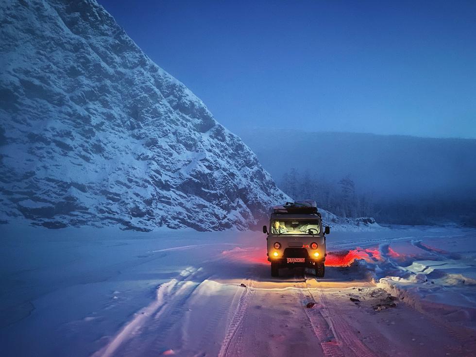 汽车停在冰雪覆盖的道路上,旁边是皑皑雪山。