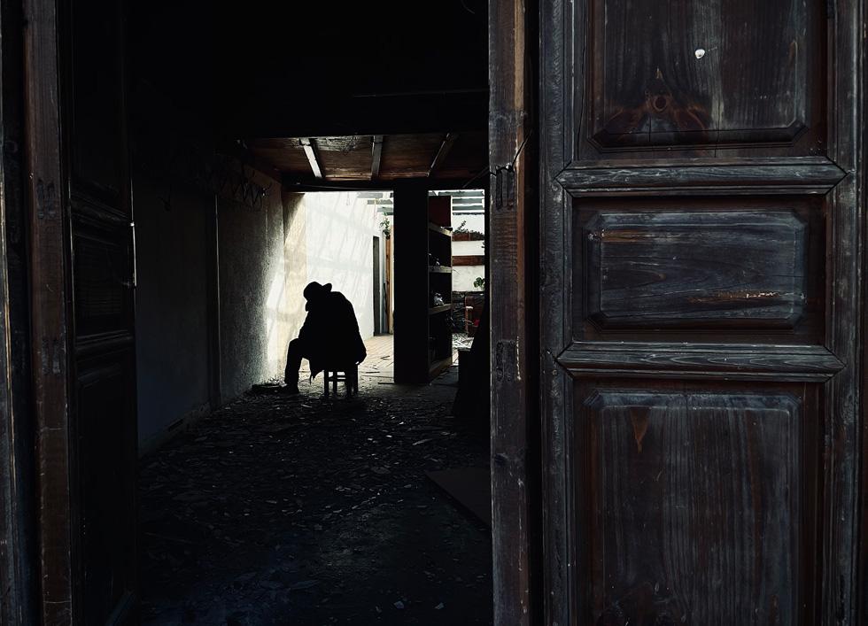 一扇敞开的门外,一个人影坐在碎片和阴影中。