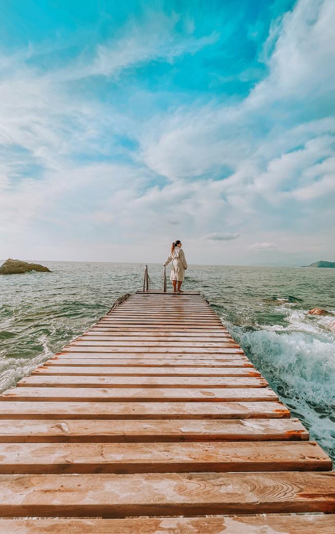 一名女子在码头边缘面水而立。