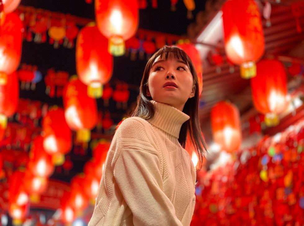 一名女子的人像照,她的头顶上悬挂着鲜艳的红色纸灯笼。