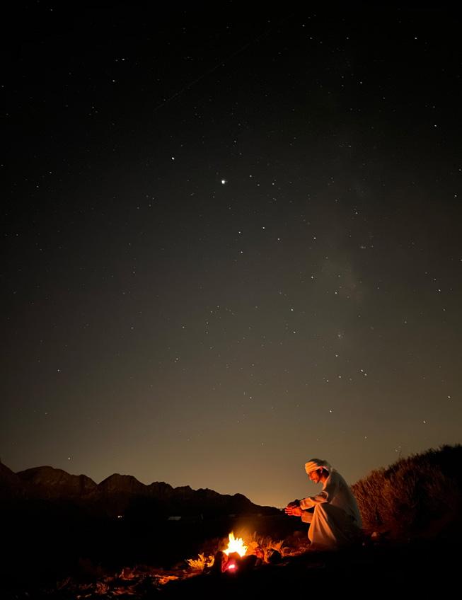 一名男子坐在沙漠中营火前的夜间人像照。